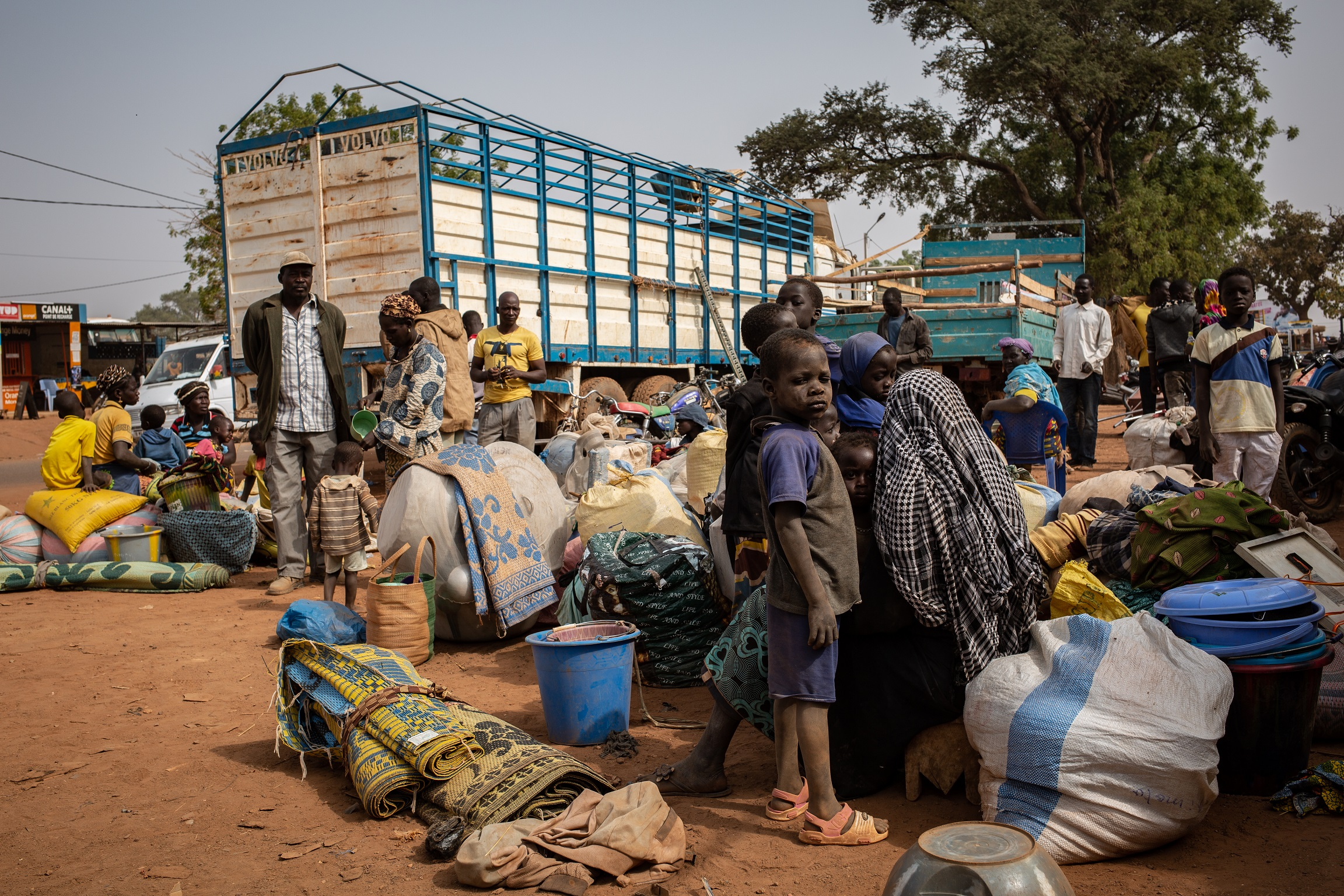 Newly displaced people waiting on the side of the road after they fled attacks in Barsalogho, Burkina Faso
